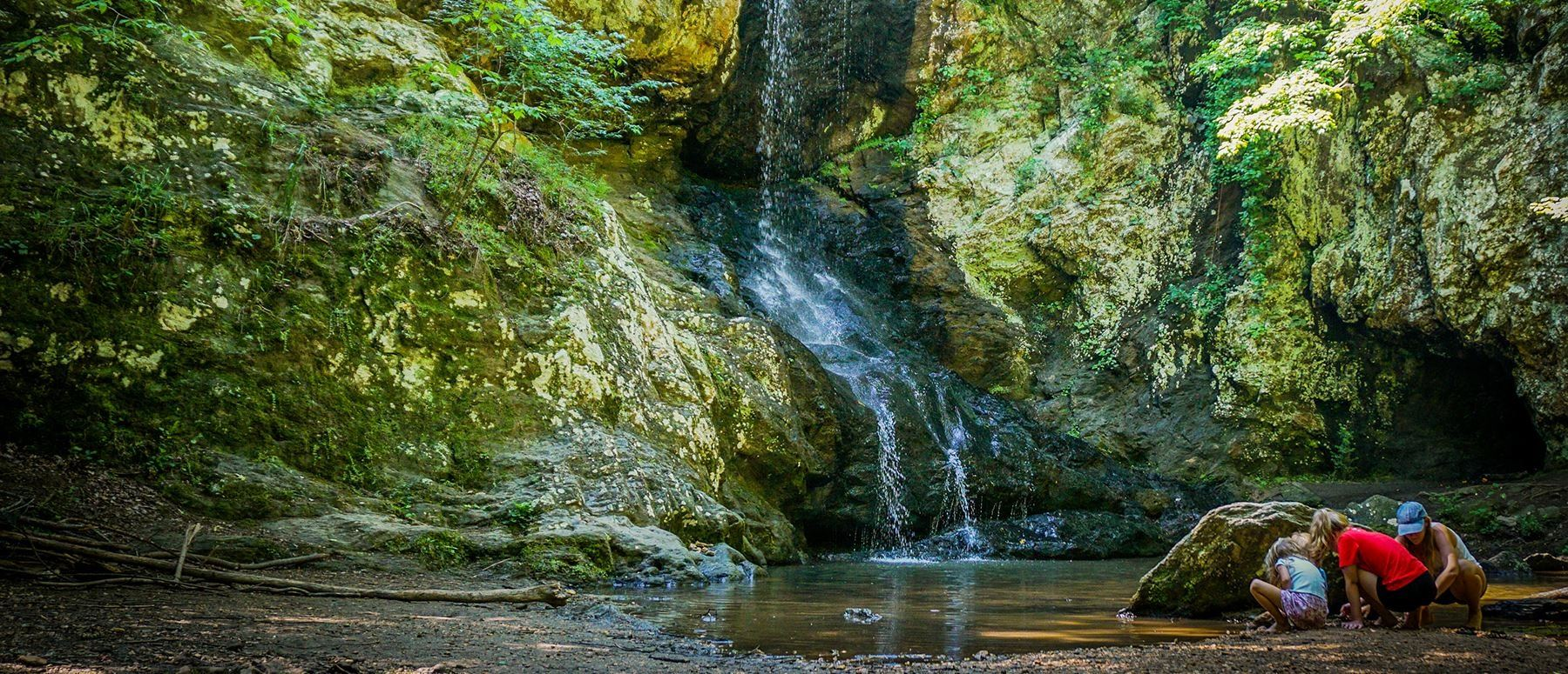 Image of a waterfall in Paulding County with a family playing in the water
