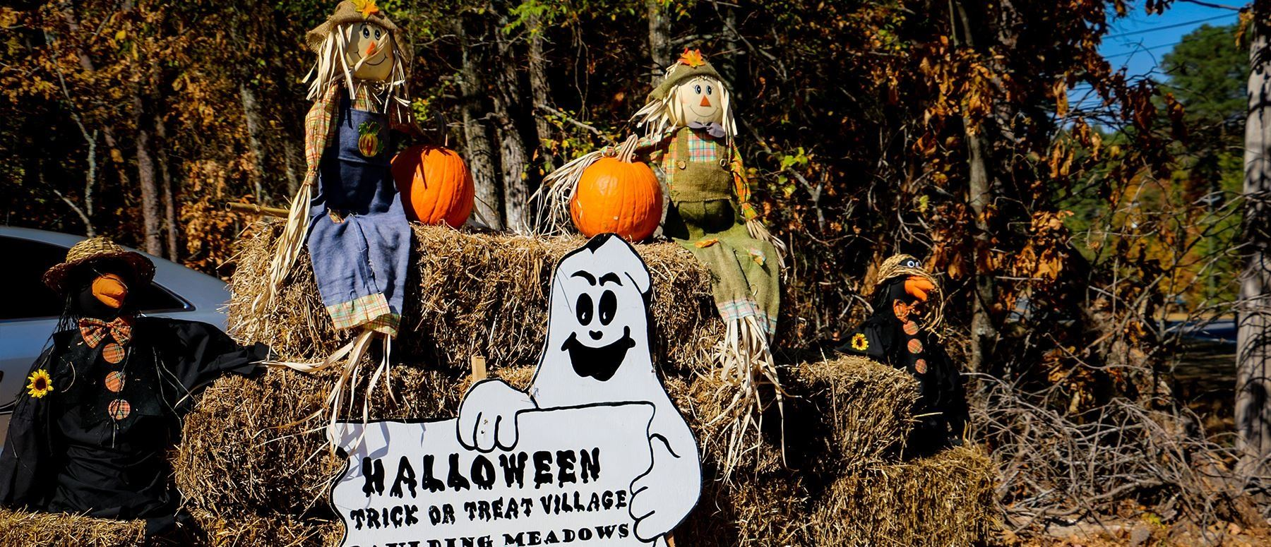 Image of some hay and scarecrows at the entrance of Paulding Meadows